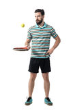 Relaxing tennis player in polo shirt bouncing ball with racket Royalty Free Stock Image