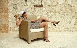 Relaxing on the terrace. Image of a wealthy woman on a rattan chair with a glass of champagne Royalty Free Stock Photography