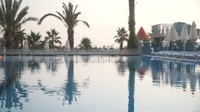 Relaxing terrace near luxury swimming pool of fancy resort and beautiful palm trees at sunset.  stock video footage