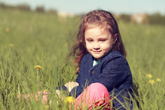 Relaxing thinking cute kid girl sitting in green grass in sunny Stock Images
