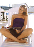Relaxing time. Girl having fun reading magazine next pool royalty free stock photos