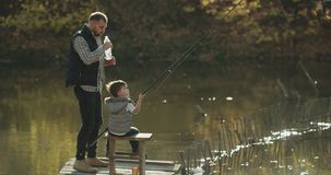 Relaxing time dad and his on fishing at lake on sunny day , teaching son to fishing , dad drinks a bottle of water. stock video footage