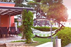 Relaxing time with a hammock in the summer garden in a luxurious hotel. Summer holidays, travel and leisure.  stock photos