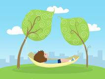 Relaxing Time. A kid lying on a hammock between two trees outside the city Royalty Free Stock Image