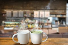 A cup of hot green tea and a cup of hot coffee at the coffee shop royalty free stock photos