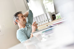 Relaxing time at work. Man in office relaxing with cup of coffee Royalty Free Stock Photos