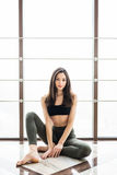 Relaxing after training. View of beautiful young woman looking away while sitting on exercise mat at gym Stock Photos