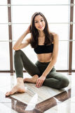 Relaxing after training. View of beautiful young woman looking away while sitting on exercise mat at gym Royalty Free Stock Image