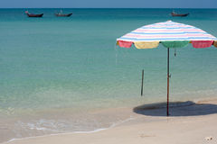 Relaxing tropical beach. Beach umbrella on tropical beach with azure blue sea Stock Images
