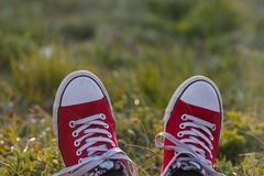 Relaxing two feet in red sneakers stock images