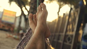 Relaxing under palms on the beach at sunset. Feet swinging in a hammock, POV. stock video