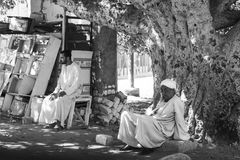 Relaxing under a tree. Two Egyptian men relaxing in the late afternoon, under a tree, in a small village Stock Image