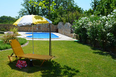 Relaxing under the umbrella. Yellow deck chair under the umbrella on green grass next to the pool Stock Photography