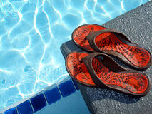 Relaxing on vacation. A neat pair of sandals await the return of their owner who is swimming in the inviting pool while on vacation Stock Images