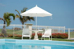 Relaxing Vacation. Patio furniture and umbrella with two chairs beside pool with and ocean background and deep blue sky Royalty Free Stock Photography