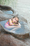 Relaxing Vacation. A little girl has found a relaxing place to take a nap in a pool of water. Nap time at the water park Stock Photos