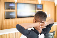 Relaxing, watching hdtv. Closeup portrait, young guy relaxing, hands folded behind head, watching TV, indoors interior background. Urban refined living stock photography