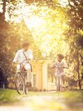 Relaxing way to school. African American father and daughter driving bike trough park stock photography