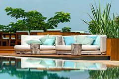 Outdoor sofa and pool. Relaxing white sofa with pillows beside swimming pool Royalty Free Stock Photography