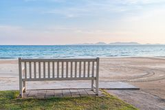 Relaxing white wooden bench at seafront. Relaxing white wooden bench at seafront with beautiful sea and mountain Royalty Free Stock Images