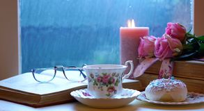 Relaxing by the window on a cold rainy day with books and cup of tea. stock image