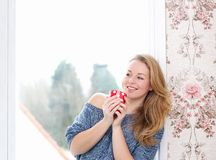 Relaxing by window with a cup of tea Stock Image