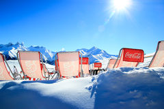 Relaxing in the winter sun. Les Sybelles ski resort, France - January 31, 2014: resting place in a mountain restaurant with Coca Cola branded sun chairs in snow Stock Photography