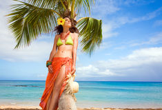 Relaxing woman. Woman relaxing on palm tree with straw hat on beach Stock Photo