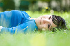 Relaxing woman. Attractive woman relaxing on grass in park Royalty Free Stock Image