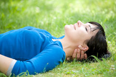 Relaxing woman. Attractive woman relaxing on grass in park Stock Image