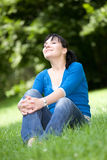 Relaxing woman. Attractive woman relaxing on grass in park Royalty Free Stock Images