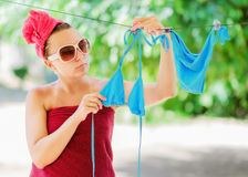 Woman dries blue bikini on clothesline Royalty Free Stock Image
