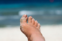 Relaxing. Woman foot with sand at the beach in sunshine Stock Images