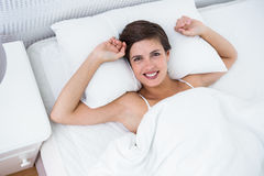 Relaxing woman in her bed smiling at camera Royalty Free Stock Image