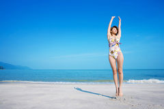 Relaxing woman jumping. A young woman with floral swimsuit by the beach relaxing jumping Royalty Free Stock Images