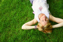 Relaxing woman laying on grass stock photo