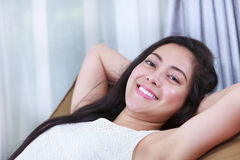 Relaxing woman lie down comfortable and smiling happy looking at Stock Photos