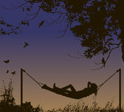 Relaxing woman lying in hammock under trees. Royalty Free Stock Photography