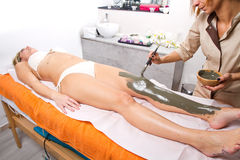 Relaxing woman lying on a massage table receiving a mud treatmen Stock Image