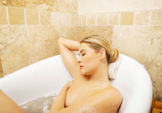 Relaxing woman propping up on bath by elbow Royalty Free Stock Photo