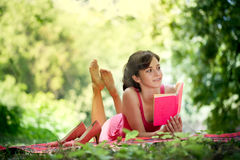 Relaxing woman reading. Beautiful woman with a happy face and reading in nature Stock Photo