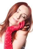 Relaxing woman in red gloves. A closeup portrait of a smiling beautiful redhead woman in red gloves isolated on white Royalty Free Stock Image