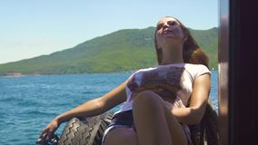 Relaxing woman resting on sea ship while cruise on blue water and gree hills landscape. Beautiful woman lying on ship stock video