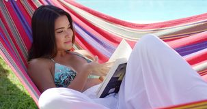Relaxing woman seated in hammock with book stock video footage