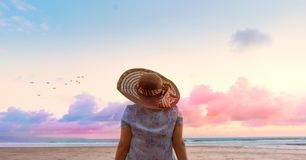 Relaxing woman sitting on the beach. Looking at sea and sky with hat. Dream travel and vacation concept.Can be used for banner royalty free stock images