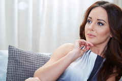 Relaxing woman sitting comfortable in sofa lounge Royalty Free Stock Photography