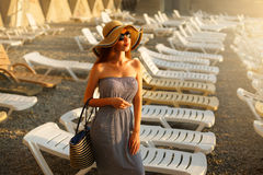 Relaxing woman with sunglusses on enjoying the summer sun happy standing in a wide sun hat at the beach with face raised Stock Photos