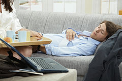 Relaxing before work. Young businessman resting on couch, woman holding breakfast tray Royalty Free Stock Image