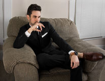 Relaxing After Work. An image of an attractive man in a suit sitting in a living room Royalty Free Stock Images