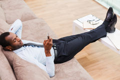 Relaxing after work done. Top view of handsome young African man in formalwear lying on the couch with his legs on a desk and holding mobile phone Stock Photos